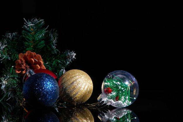 Decorazioni natalizie e rami di abete rosso su sfondo nero.