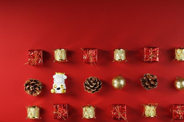 Decorazioni natalizie e giocattoli con una mucca su uno sfondo rosso