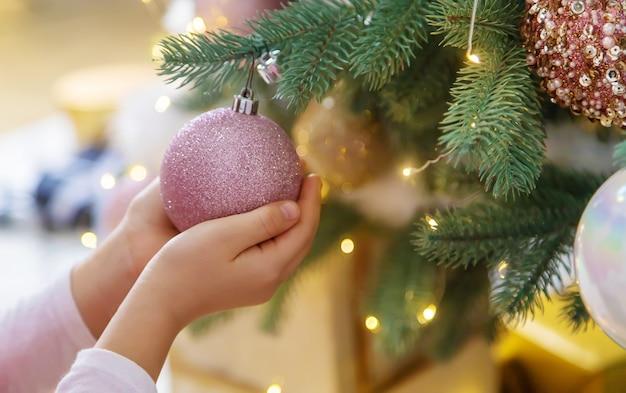 Addobbi natalizi sull'albero nelle mani di un bambino. messa a fuoco selettiva. vacanza.