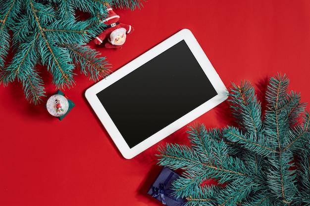Decorazioni natalizie e tablet bianco con schermo nero su sfondo rosso caldo. tema di natale e capodanno. posto per il tuo testo, desideri, logo. modello. vista dall'alto. copia spazio. natura morta. disposizione piatta.