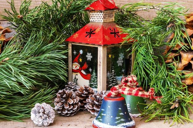 Decorazioni natalizie con lanterna, giocattoli, campane, coni e albero di capodanno.
