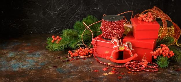 Decorazioni natalizie con luci, giocattoli e scatole regalo rosse su oscurità