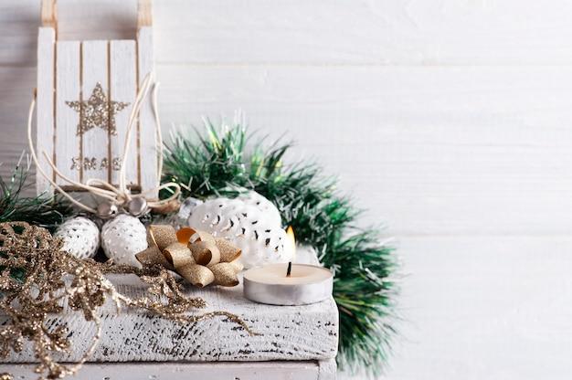 Addobbi natalizi con slitta in legno e fiocco dorato