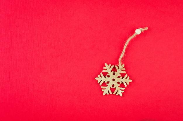 Fiocco di neve di legno delle decorazioni di natale sul concetto rosso di festa del fondo
