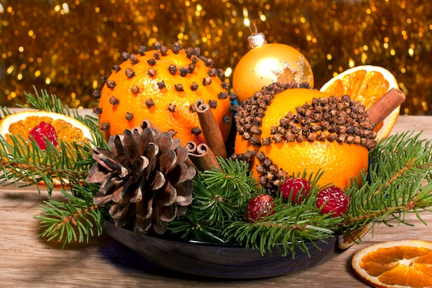 Composizione decorativa di natale con pomander arancioni vicino su uno sfondo di legno