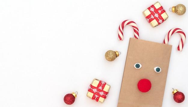 Cervo di natale fatto di borsa artigianale e due canne di natale con scatole regalo, palline rosse e oro su sfondo bianco. stile piatto laici con spazio di copia.