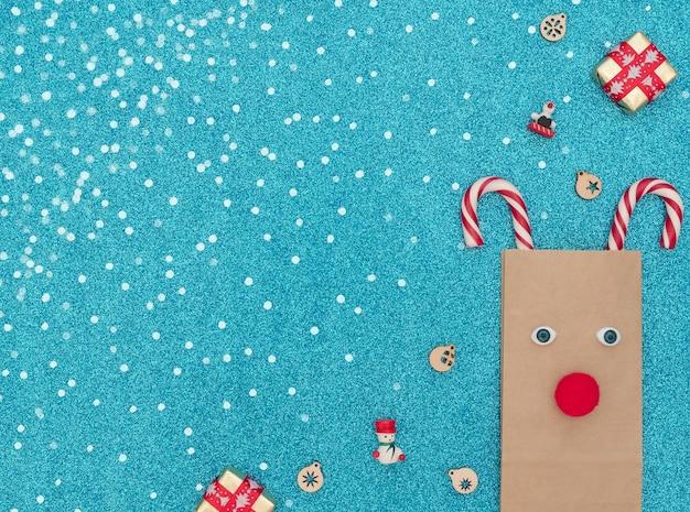 Cervo di natale fatto di borsa artigianale e due canne di natale con due scatole regalo e decorazioni in legno su sfondo blu con neve bianca. biglietto d'auguri