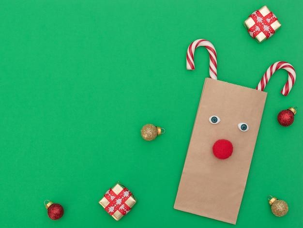 Cervo di natale fatto di borsa della spesa artigianale e due canne di natale con scatole regalo e palline di natale su sfondo verde. stile piatto laici con spazio di copia.