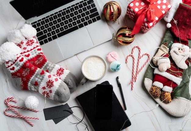Desktop natalizio con laptop, tablet e smart phone circondato da calze, bastoncini di zucchero e caffè