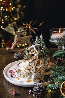 Dolce natalizio, rotolo di meringa decorato con casa di marzapane