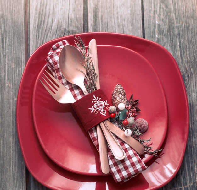 Posate di cena di natale con decorazioni su un tavolo di legno