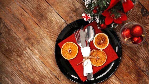 Decorazione della cena di natale con arance essiccate e un tovagliolo rosso su un piatto nero