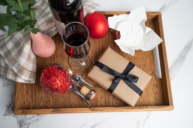 Cena di natale servita su vassoio in legno. vino, formaggio, palline di natale e un regalo incartato, vista dall'alto. foto di alta qualità