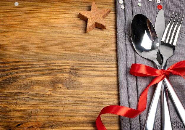 Tavola da pranzo di natale con posate, tovagliolo grigio e vista dall'alto di spezie invernali.