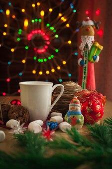 Bevanda di natale con biscotti fatti in casa al cioccolato decorati con luci scintillanti e giocattoli