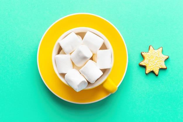 Bevanda di natale con marshmallow in tazza gialla con piattino su sfondo verde, vista dall'alto.