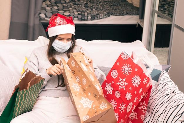 Natale durante la pandemia di coronavirus covid 19, la giovane donna in maschera medica a casa guarda i regali di capodanno nelle borse