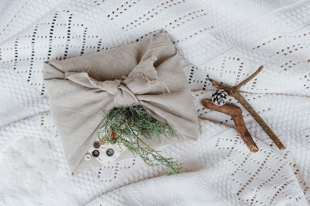 Carta da regalo ecologica natalizia in tradizionale stile furoshiki giapponese su fondo bianco lavorato a maglia. incartare regali con le tue mani.
