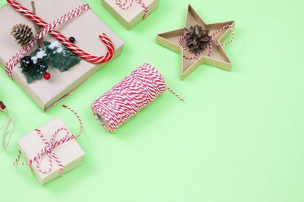 Regali di imballaggio ecologici di natale su verde, concetto di vacanza natalizia eco, sfondo invernale festivo di decorazioni ecologiche. presente con caramelle e abete, scatole di carta e albero giocattolo in legno sul verde