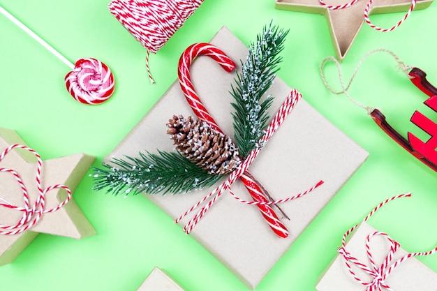 Regali di imballaggio ecologici di natale su verde, concetto di vacanza natalizia eco, superficie invernale festiva di decorazioni ecologiche. presente con caramelle e abete, scatole di carta e albero giocattolo in legno