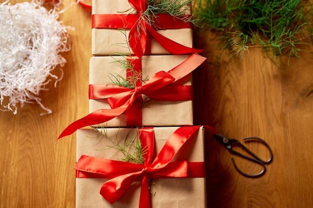 Carta kraft di imballaggio ecologico di natale e rami di abete regali per le festività natalizie, natale su tavola di legno, arredamento ecologico, confezione regalo regalo di natale