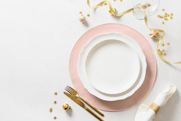 Regolazione della tavola di eleganza di natale con decorazioni rosa e dorate su bianco.