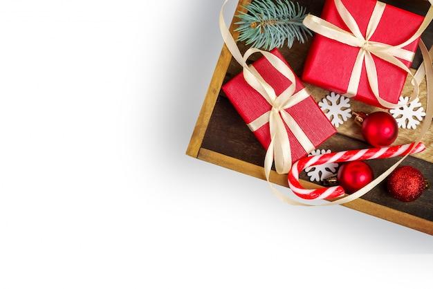 Elemento di natale per il design. scatola di legno con scatole regalo rosso con nastro, giocattolo di natale, rami di abete, caramelle di natale, fiocchi di neve, isolamento su sfondo bianco. vista dall'alto. disteso