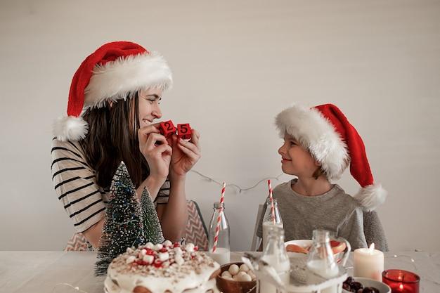Cena di natale in famiglia. la mamma mostra a suo figlio un calendario con il numero 25 al tavolo delle vacanze.