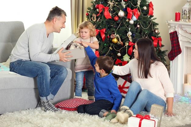 Ritratto di famiglia di natale nel soggiorno di casa per le vacanze, al mattino