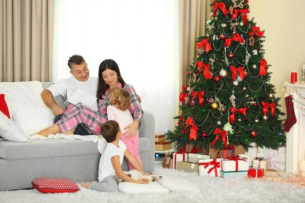 Ritratto di famiglia di natale nel soggiorno delle vacanze di casa, al mattino