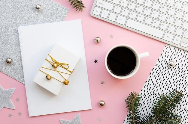 Scrivania femminile di natale con rivista vuota, computer, decorazioni natalizie e confezione regalo