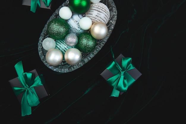 Scatole regalo natalizie nere con nastro verde su glitte di velluto