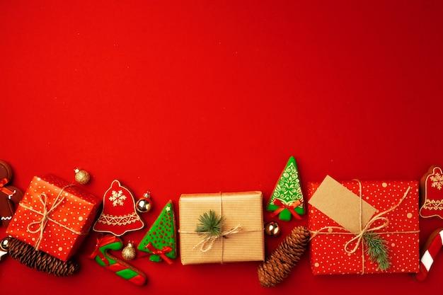 Cartolina di natale festiva con regali avvolti e biscotti di pan di zenzero sul rosso