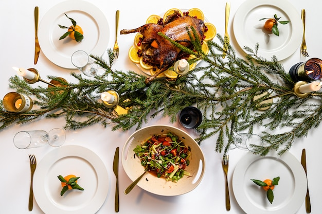 Cena festiva natalizia. pasto tradizionale delizioso di festa e mani delle persone che li mangiano. tavolo decorato con gustosi piatti. flat ley. tavolo bianco