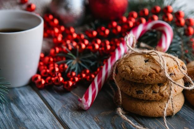 Concetto festivo dello spuntino dell'alimento di natale. mucchio di biscotti al cioccolato e una tazza di tè su fondo di legno. decorazione stagionale di perline rosse sullo sfondo.