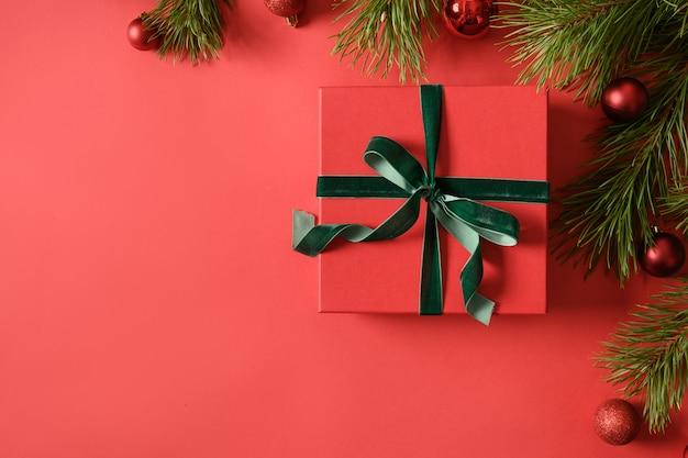 Cartolina d'auguri festiva di natale con regalo rosso, rami su sfondo rosso.