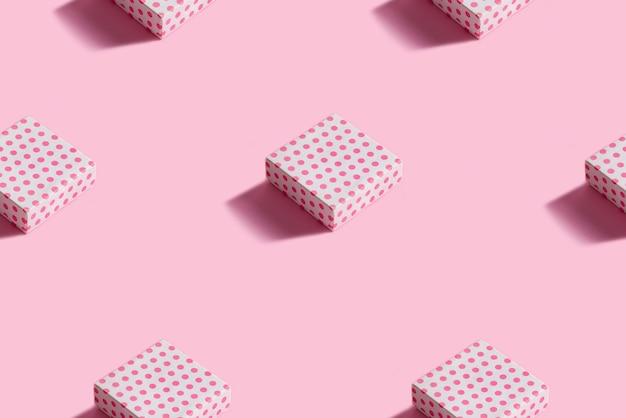 Modello festivo di natale da scatole regalo avvolte in carta decorativa colorata su un rosa pastello