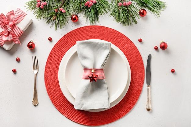 Regolazione festiva della tavola di natale con le decorazioni di festa bianche e rosse, regalo sulla tavola bianca. vista dall'alto.