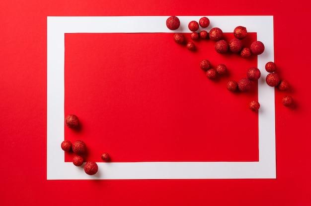 Tavola festiva di natale. cornice bianca con decorazioni natalizie rosse sulla tavola rossa. posto per il testo. vista dall'alto