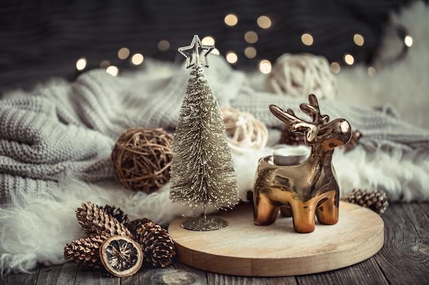 Tavola festiva di natale con cervi giocattolo, tavolo sfocato con luci dorate e candele