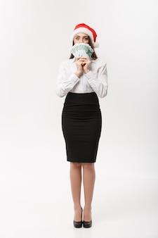 Concetto di natale e finanza giovane donna d'affari che mostra denaro chiudendo il viso con espressione di sorpresa