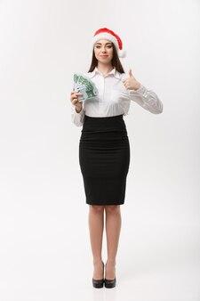 Concetto di finanza e natale giovane donna d'affari che mostra denaro e pollice in su
