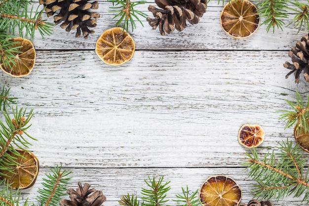 Rami di abete di natale con coni e fetta di limone secca. vista dall'alto con copia spazio per il tuo testo