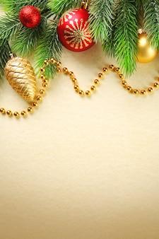 Rami di abete di natale con giocattoli e perline su sfondo di carta