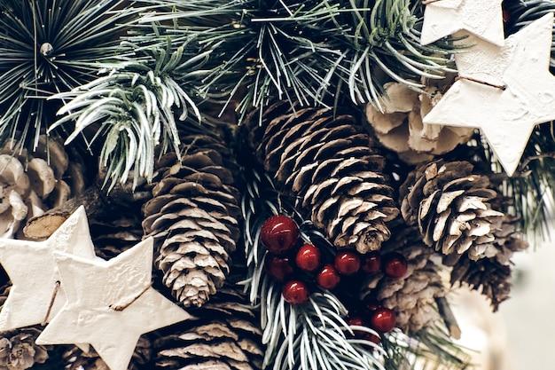 Brunch dell'albero di abete di natale con bacche rosse, candele a stella e coni nella neve scintillante vicino texture