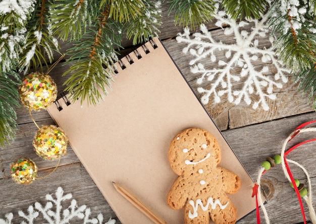 Abete di natale coperto di neve, decorazioni e blocco note vuoto su sfondo di tavola di legno
