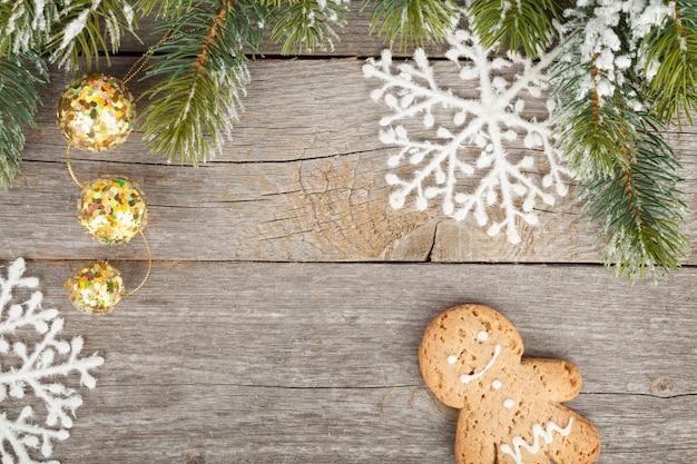 Abete di natale e decorazioni ricoperte di neve su sfondo di tavola di legno