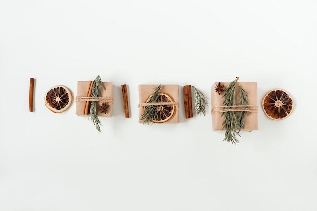 Composizione piatta di natale di confezioni regalo artigianali sulla scatola di carta marrone fatta a mano con ramo di albero di natale e bastoncini di cannella e arancia secca.