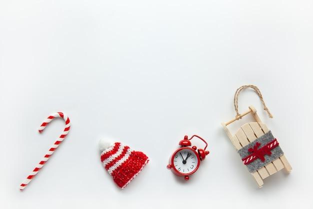 Christmas flat lay, winter beanie hat, candy cane, piccolo orologio analogico rosso, slitta su sfondo bianco,