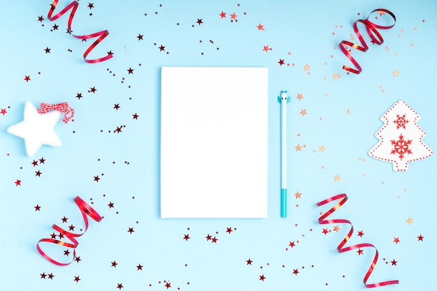 Piatto di natale laici con decorazioni, taccuino e penna su carta blu